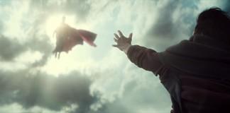 person reaching towards Superman